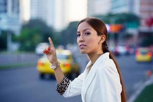 latina businesswoman calling taxi car leaving work photo