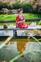 Mujer pensativa en traje de geisha en jardín en el puente