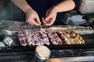Japanese man making traditional skewers