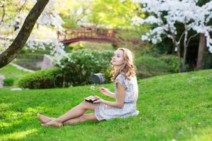 Joven mujer europea comiendo sushi en el parque japonés foto