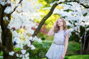 hermosa niña en el jardín de los cerezos en flor foto