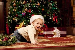 Baby near the Christmas tree. Little boy celebrating Christmas.