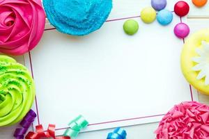 Blank card surrounded by brightly colored cupcakes