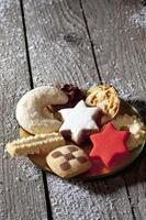 Selection of christmas cookies on plate on wooden floor