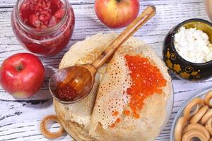 Shrove Tuesday pancakes with red caviar on a white table photo