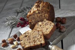 kerst fruitcake met noten en kerstversiering op een houten bord