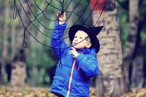 little boy in halloween costume playing with spider web
