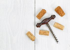 Vintage corkscrew with old corks on white wooden boards