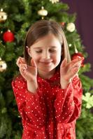 Young Girl Crossing Fingers In Front Of Christmas Tree