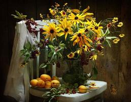 Still life with yellow flowers and apricots photo