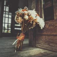Beautiful white wedding bouquet on wooden background. photo