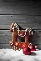 Christmas gingerbread horse christmas bulbs against wooden background photo