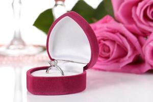 Rosa vino espumoso en copas y rosas aislado en blanco foto