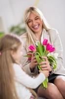 mamá feliz recibiendo flores de su hija