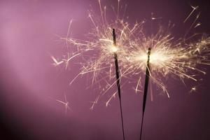Burning sparklers on pink background