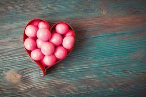 Sweet candies in heart shaped boxes on vintage wooden background