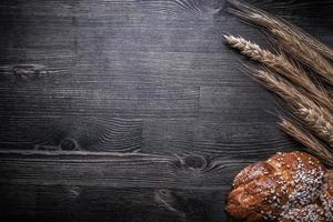 Composition of bread wheat and rye ears on wooden board