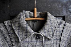 Vintage grey coats collar on the wooden black wardrobe photo