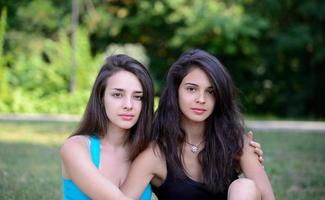 Two beautiful girls hugging in the park photo