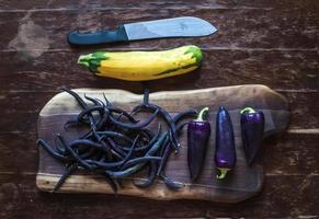 Violet chili peppers, beans and yellow zucchini on rustic wooden