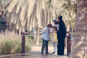 Middle Eastern Family Using Smart Phone Outdoors photo