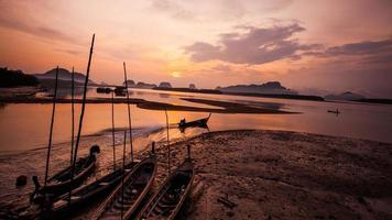 silueta de pescador y barcos tradicionales tailandeses en sam chong