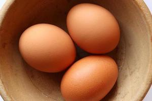 Three eggs in a wooden bowl