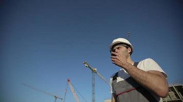 engenheiro construtor usando um walkie-talkie dando instruções video