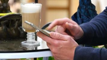 Male hands using smartphone and having cappuccino at cafe in shopping mall. Close-up of man browsing information and scrolling pictures on smart phone video