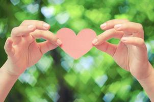Hands holding paper heart on heart bokeh background photo