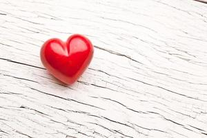 Red heart on a white wooden table