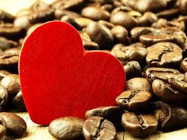 Heart and Coffee beans close-up on wooden, oak table. photo