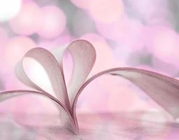 Heart shape from opened book pages with bokeh background.