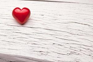 Red heart on a wooden table.