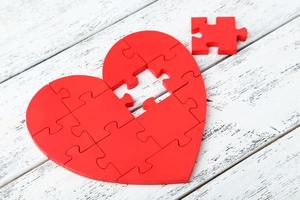 Corazón de rompecabezas rojo sobre fondo blanco de madera