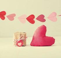 guirnalda de corazones sobre una pequeña caja de regalo y un cojín de corazón rojo