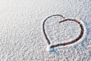 Heart drawn in snow. Symbol of love. Winter sunny day.