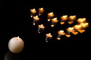 vela branca com formas de coração chamas de velas