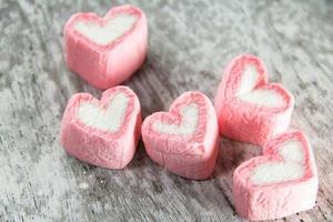 marshmallows love on white wood