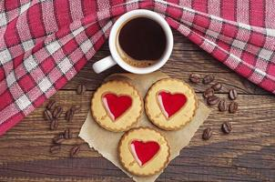 taza de café y galletas con mermelada de fresa foto