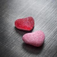 Candy in shape of hearts on wooden background