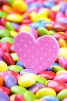 Pink heart and colorful chocolate smarties photo