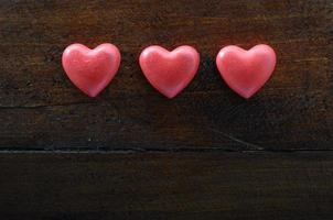 Three red heart on wooden background