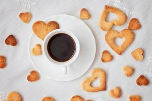 Sweet cookies in heart shape and cup of coffee