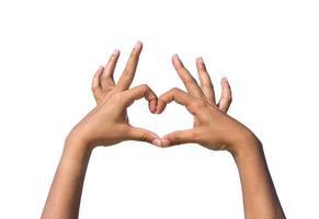 Manos de niña formando corazón de amor sobre fondo blanco. foto