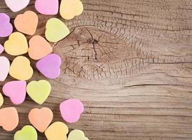 Colorful candy hearts on wood background photo