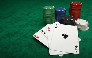 cuatro ases con fichas de juego sobre fieltro verde
