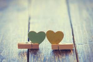 Two hearts shape toys with pins on wooden background. photo