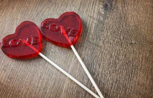 Caramelos rojos con cobertura en forma de corazón sobre fondo de madera