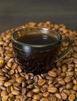 Granos de café, taza sobre fondo oscuro foto